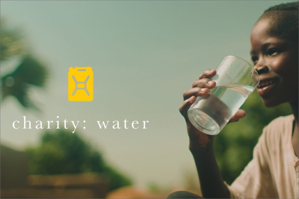 charity: water, boy holds glass of water in hand