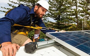 Man wearing hard hat and harness on top of roof installs solar panel system