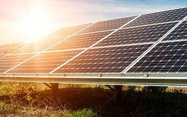 Sun gleams of solar panel in green field below a blue sky