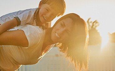 Woman smiles with child on back as the sun shines